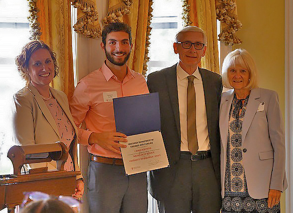 Cameron Hunter, second from left, receives a Champion of Change Award from Gov. Tony Evers, third from left.