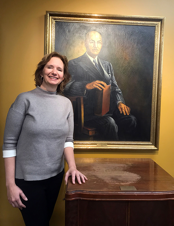 Stephanie Nelson Perry saw the official portrait of her great-grandfather, Burton Nelson, when she visited UW-Stout recently for the first time. In front of the portrait is a cabinet that belonged to Nelson