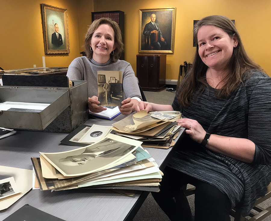 Perry provided University Archivist Heather Stecklein, right, with photos and family history related to her great-grandfather, former UW-Stout President Burton Nelson. Between them in the background is Nelson's portrait.