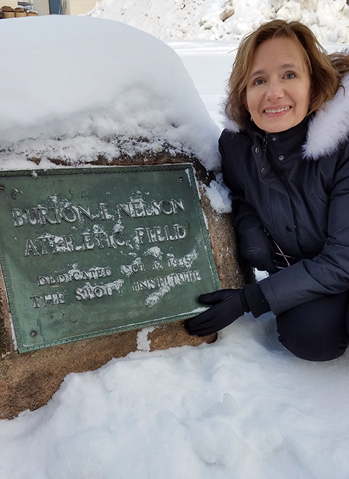 Nelson Field at UW-Stout was named after Burton Nelson when it was dedicated in 1935, while he still was president. His great-granddaughter, Stephanie Nelson Perry, pushed away snow to see the dedication plaque during a recent visit to campus.