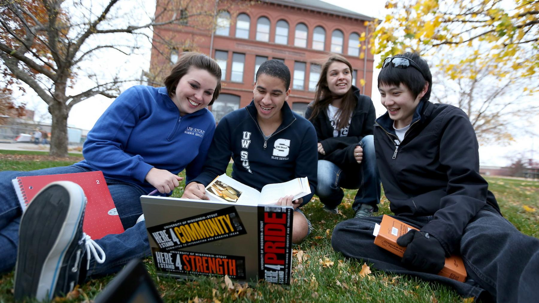 UW-Stout students lounge and study on the campus lawn.