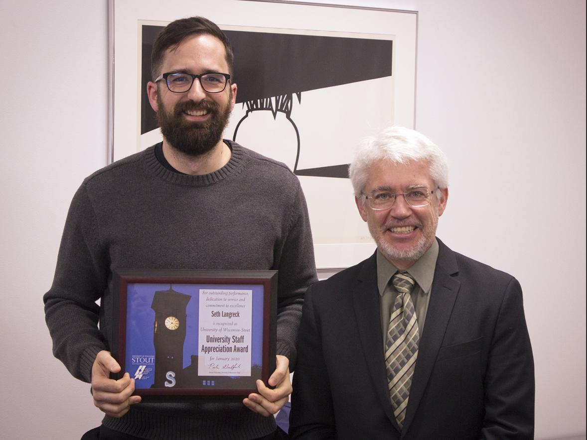 Seth Langreck, left, received the University Staff Employee Appreciation Award for January at UW-Stout from interim Chancellor Patrick Guilfoile.