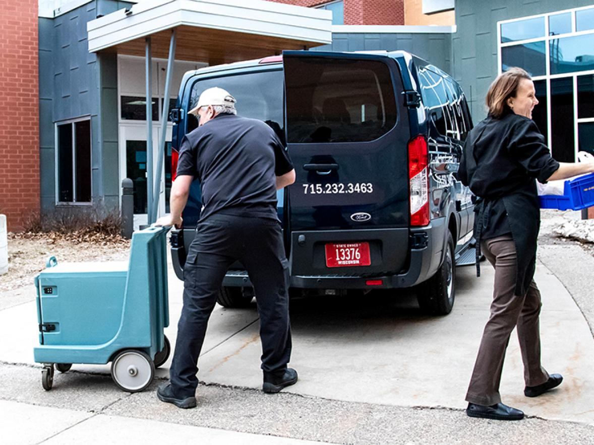 University Dining staff David Leach, at left, and Lindsay Schade deliver meals to a residence hall.