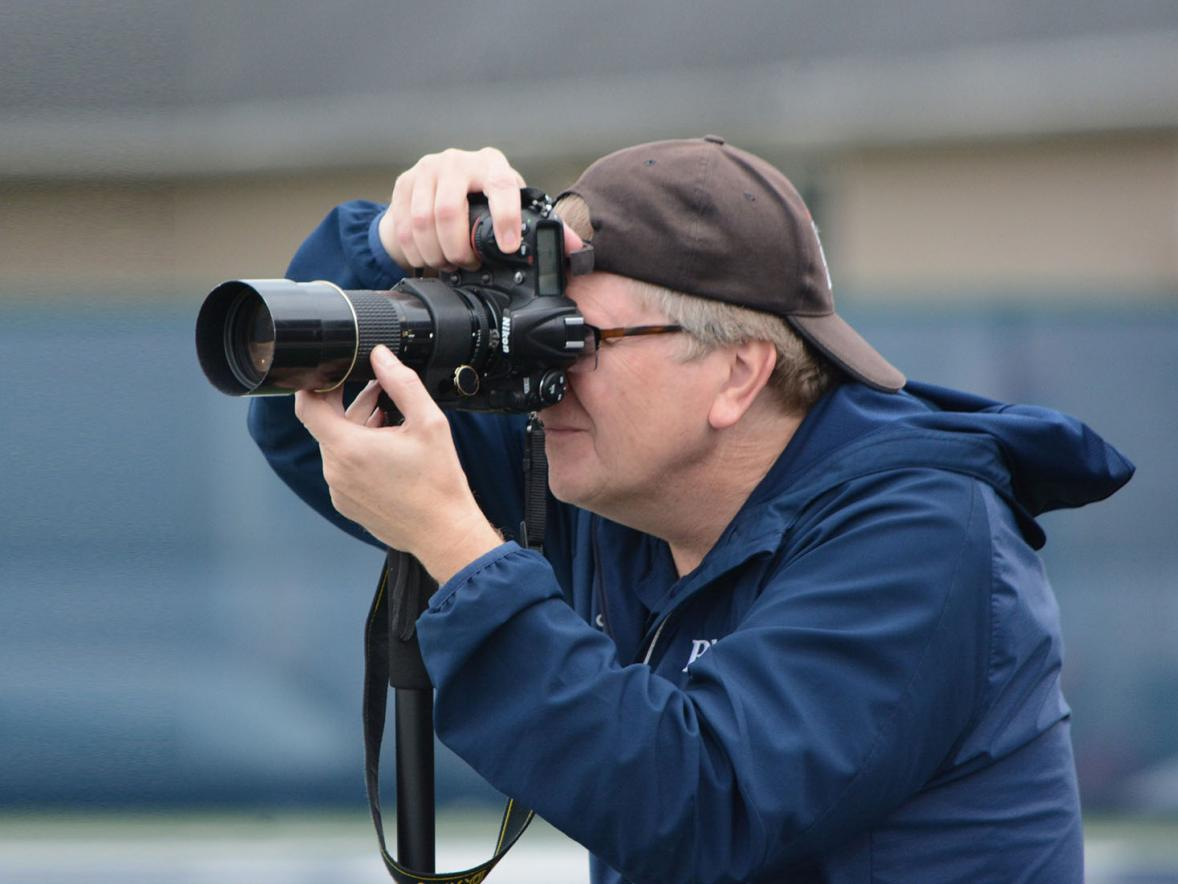 Layne Pitt, UW-Stout's sports information director, takes photos at a football game. Pitt received a 25-year-award recently from the College Sports Information Directors of America.