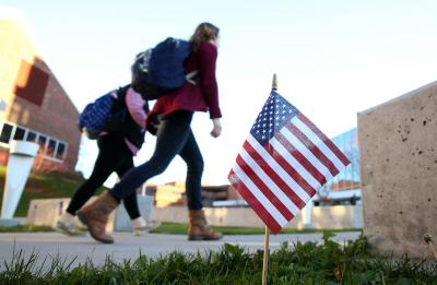 UW-Stout students walk across campus amid American flags, celebrating our veterans.