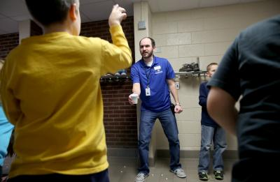 UW-Stout alumni Ashley DeMuth and Josh Sales lead the Menomonie chapter of the Boys & Girls Club of the Greater Chippewa Valley, which opened in October 2014 at River Heights Elementary School. Sales, who serves as the Club's program coordinator, is pictured leading an activity with students in the after school program